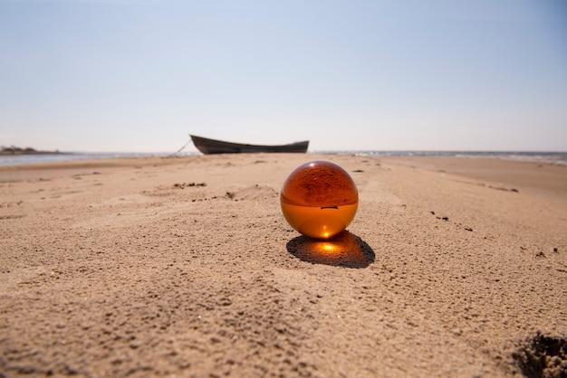 Sfera di vetro arancione sulla sabbia vicino al mare