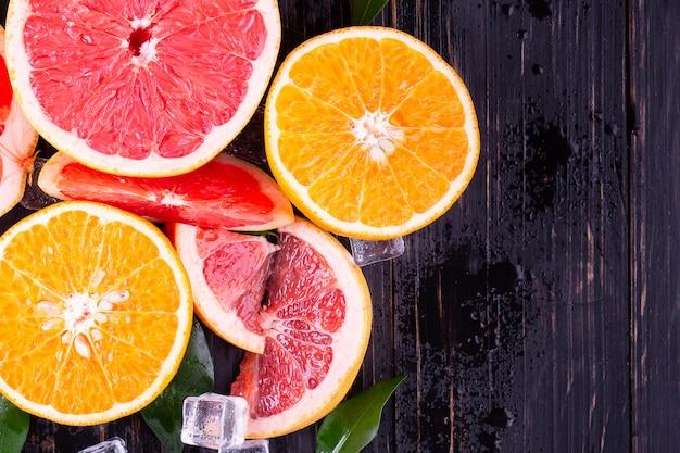 Succo d'arancia e pompelmo su uno sfondo nero in legno