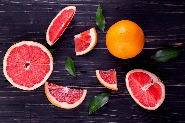 Succo di arancia e pompelmo su sfondo nero in legno