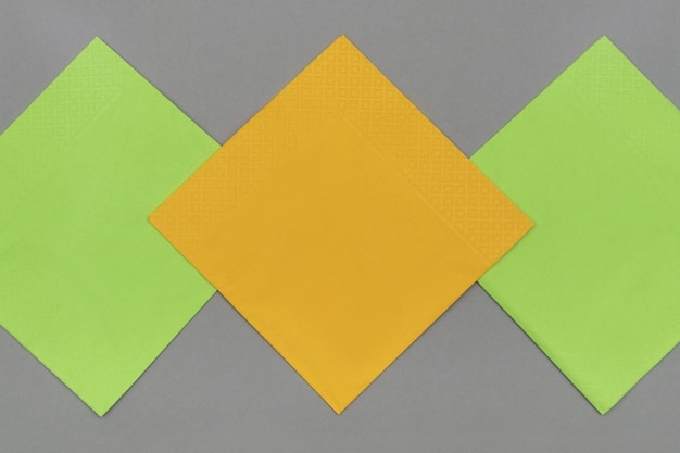 Tovaglioli di carta arancione e verde su sfondo di carta grigia, vista dall'alto.