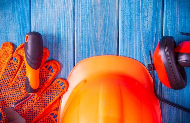 Cappello duro arancione e strumento sui bordi blu d'annata di legno