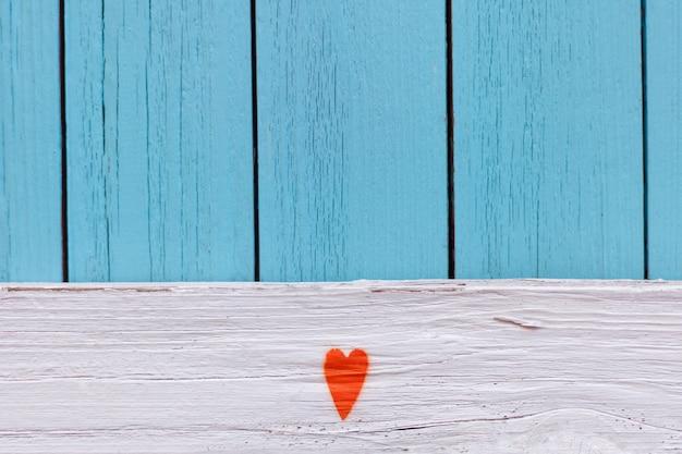 Cuore arancione dipinto sul fondo di struttura del grano di legno di lerciume del ragazzo dell'annata afflitto. parete di legno strutturata blu. legno malandato