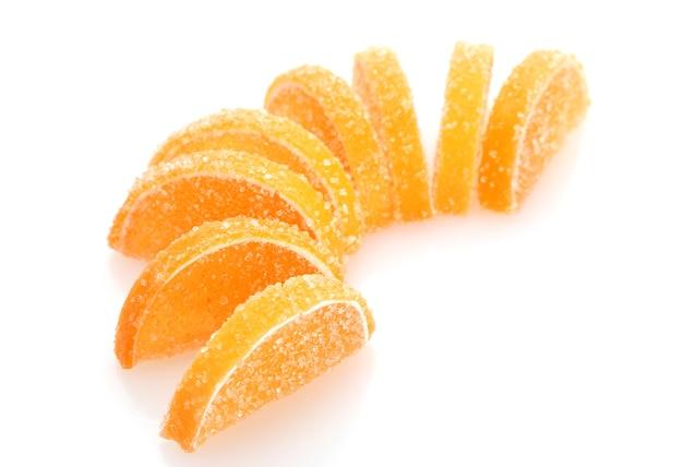 Caramelle di gelatina arancione isolate su bianco