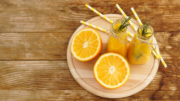 Succo d'arancia in bottiglie di vetro decorate con un rametto di rosmarino