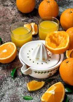 Succo d'arancia in un bicchiere e uno spremiagrumi. su fondo rustico
