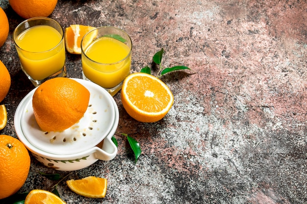 Succo d'arancia in un bicchiere e uno spremiagrumi.