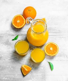 Succo d'arancia in brocca di vetro e arance fresche.