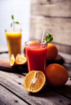 Succo d'arancia in vetro con menta, frutta fresca sulla tavola di legno