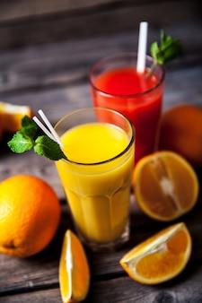 Succo d'arancia in vetro con menta, frutta fresca su legno