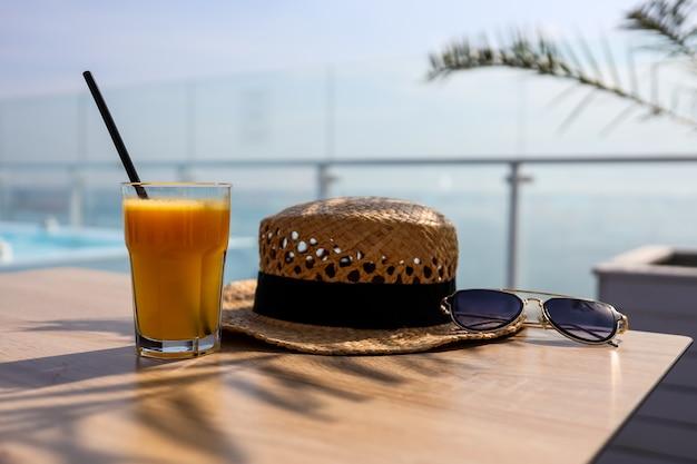 Succo d'arancia, cappello di paglia e bicchieri in un caffè sullo sfondo del mare.