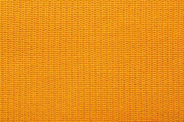 Reticolo lavorato a maglia arancione dei filati acrilici, primo piano. sciarpa in lana lavorata a maglia trama gialla.