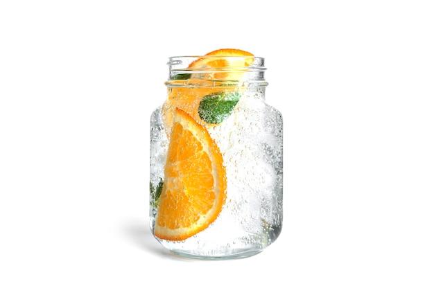Limonata all'arancia con menta e ghiaccio in un barattolo di vetro trasparente isolato