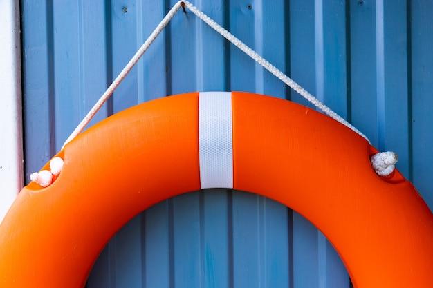Salvagente arancione appeso al muro, porta.