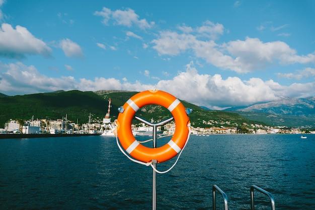 Salvagente arancione su un metallo in piedi vicino alle montagne, all'acqua e al cielo.