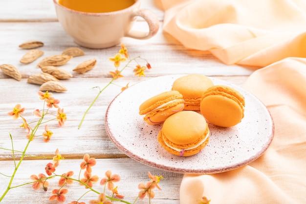 Macarons arancioni o amaretti torte con una tazza di succo di albicocca su un bianco di legno
