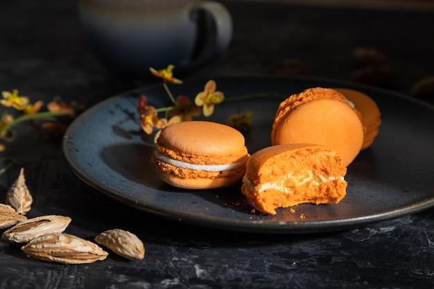 Macarons o amaretti arancioni torte con una tazza di caffè su un nero