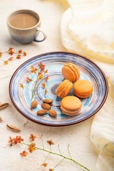 Macarons o amaretti arancioni torte con una tazza di caffè su uno sfondo di cemento bianco e tessuto di lino. vista laterale,