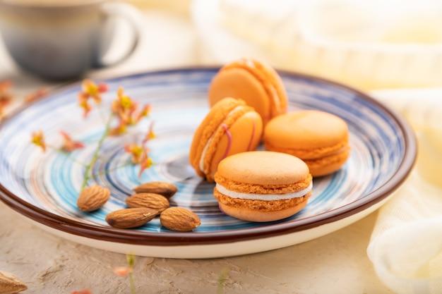 Macarons o amaretti arancioni torte con una tazza di caffè su un bianco