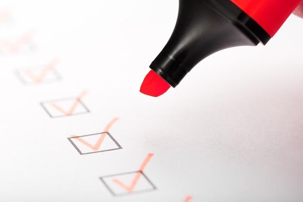 Pennarello arancione con pennarelli sul foglio della lista di controllo. elenco di controllo completato il concetto di attività.