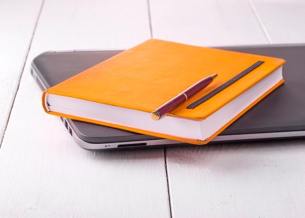 Taccuino arancione con una matita sdraiata su un laptop tra sfondi di legno
