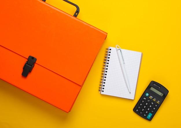 Cassa, taccuino e calcolatrice di carta arancione su un colore giallo.