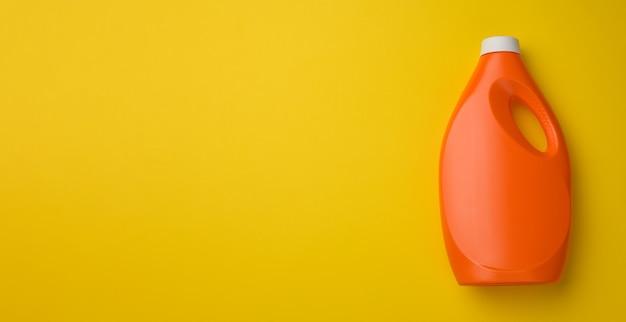 Bottiglia di plastica arancione per detersivo liquido in polvere su sfondo giallo, vista dall'alto, spazio copia