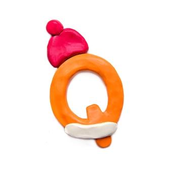 Lettera p di plastilina arancione dell'alfabeto in un cappello invernale rosso su sfondo bianco