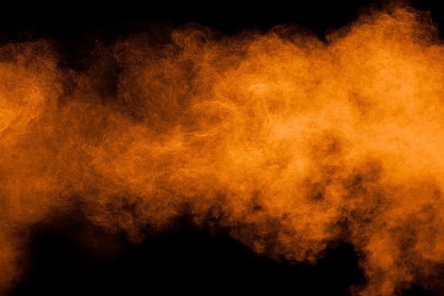 Esplosione di polvere arancione su sfondo nero. spruzzata di polvere di colore arancione.