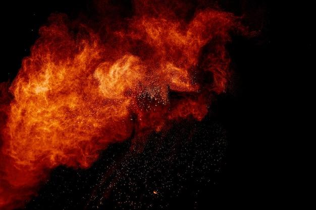 Polvere arancione schizzata su sfondo nero. contesto astratto della nuvola di polvere.