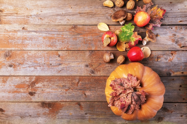 Zucca arancione con funghi cardoncelli, mele, noci e foglie colorate su vecchie tavole di legno rustici. sfondo autunno giorno del ringraziamento
