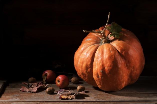 Zucca arancione con funghi cardoncelli, mele, noci e foglie colorate su vecchie tavole di legno rustici. autunno giorno del ringraziamento