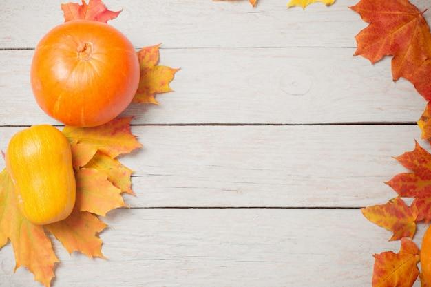 Zucche arancioni con foglie di autunno sul vecchio legno bianco