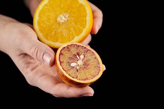 Metà della frutta arancia rossa e arancia rossa nelle mani su sfondo nero