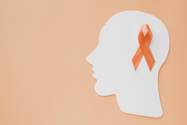 Nastro arancione sul cervello della testa di carta, consapevolezza dell'adhd