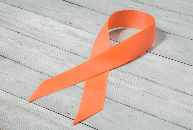 Nastro arancione su fondo di legno, simbolo del problema della violenza contro le donne, associazione del cancro del rene, simbolo di solidarietà