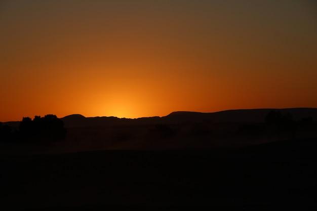 Cielo arancione dal campo berbero del deserto di merzouga nelle dune dell'erg chebbi. marocco