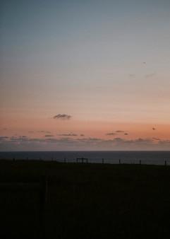 Cielo arancione sopra la cupa spiaggia recintata
