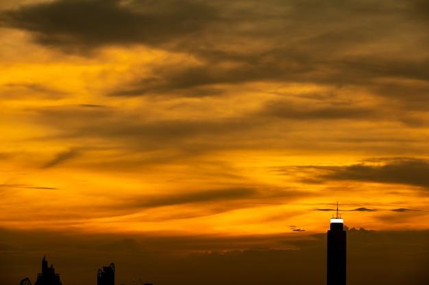 Cielo arancione e tramonto alla città di bangkok con edificio per uffici