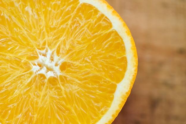 Fetta d'arancia frutti sani concetto, close up frutti arancioni su sfondo di legno