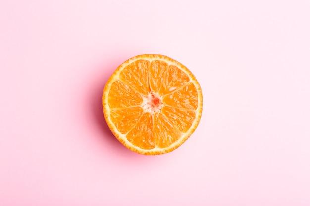 Fetta d'arancia su uno sfondo rosa minimo. arancio succoso brillante su una priorità bassa isolata in bianco dentellare. estate, sole, concetto di salute.