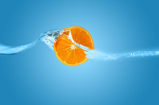 Fetta d'arancia lavata con acqua pulita su sfondo blu