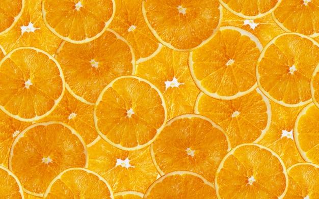 Sfondo senza giunte di fette d'arancia. taglia gli agrumi gialli.