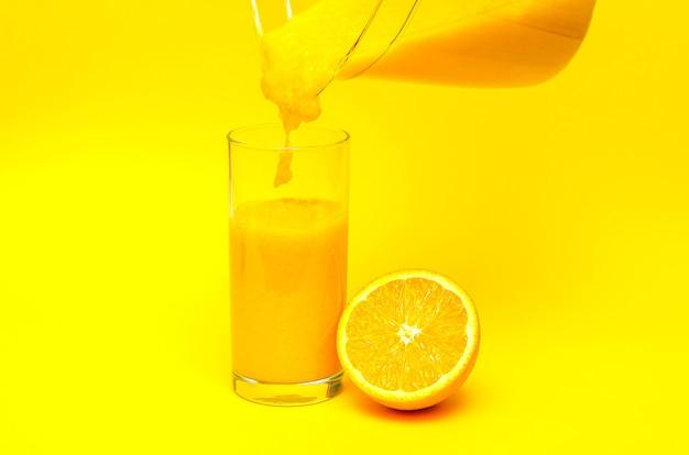 Frullato di arancia su sfondo giallo, frullato fatto in casa, frullato di vetro