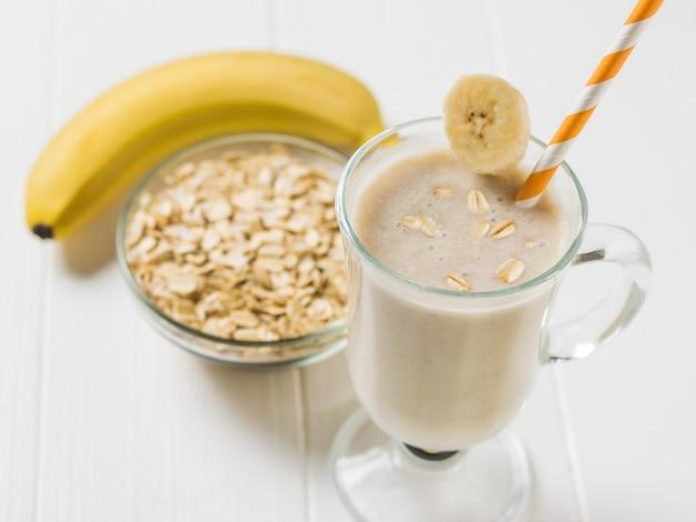 La cannuccia d'arancia nel bicchiere con frullati di farina d'avena alla banana su un tavolo bianco. frullato vegetariano. nutrizione sportiva.