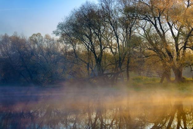 Alba arancione sulla superficie del fiume con nebbia
