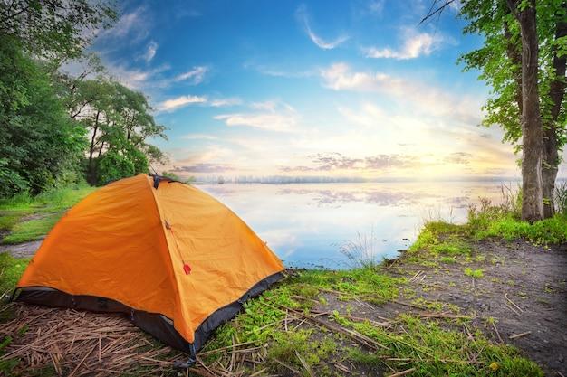 Tenda arancione in riva al lago al tramonto