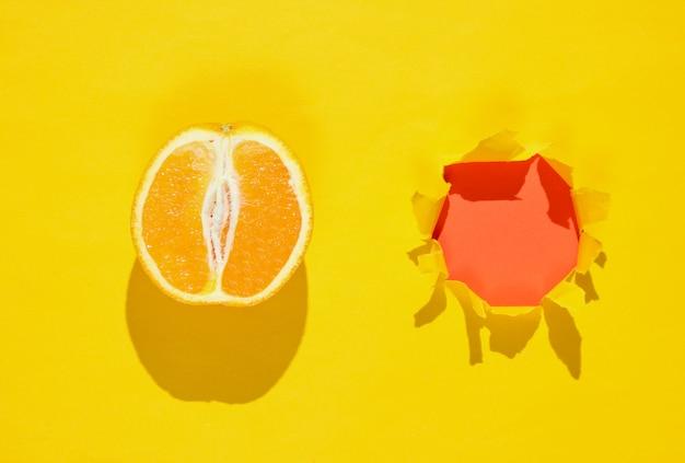 Arancione e un buco strappato in carta gialla. concetto di frutta minimalista
