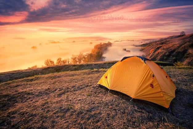 Tenda turistica arancione sulla collina sopra il fiume nebbioso