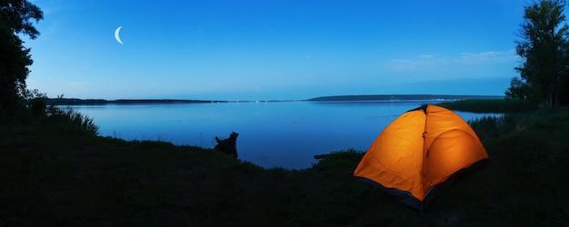 Tenda turistica arancione sulla riva del lago al crepuscolo