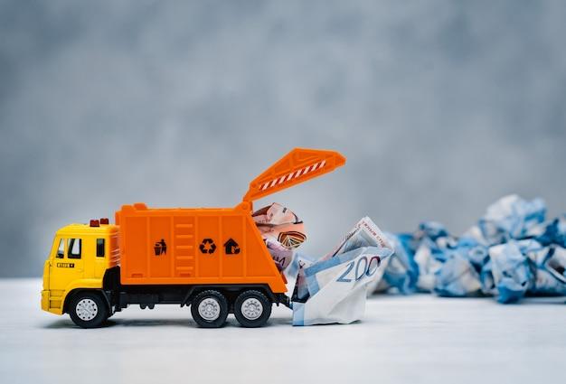 Il camion della spazzatura arancione del giocattolo scarica le banconote di carta sgualcite